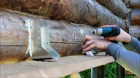 recess : Assembling a wooden frame and building a house. Russia. The worker fixes fastenings for floor construction in a wooden house, drills screw holes with a drill tool.