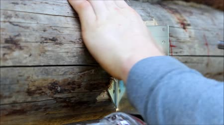 recess : Assembling a wooden frame and building a house. Russia. The worker screw the screws into the pre-drilled holes with a screwdriver. Stock Footage