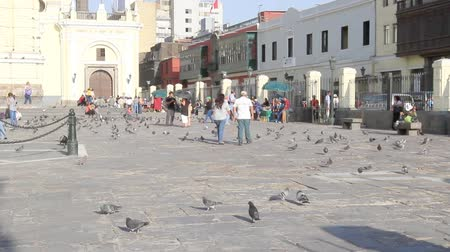 Church square with pigeons and people on a Sunday morning in Peru