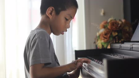 fortepian : Asian boy learning to play piano