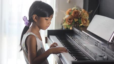 fortepian : Asian girl learning to play piano