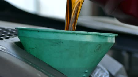 petrol : motor oil being poured into a funnel