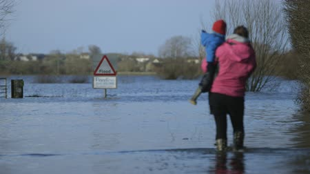 inglaterra : Classic shot of mother and child walking in flood water in front of flood sign