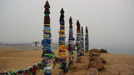 relict : Wooden poles on the island of Olkhon, interlaced with numerous ribbons of different colors of blue, orange, red, green, and all of them are developed in the wind. These tapes tied around poles and tourists visit the island as amulets and promises given to