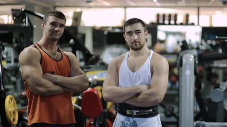 powerlifter : Two men stand in the middle of the hall with numerous equipment and simulators, hands crossed on his chest and look confidently into the camera