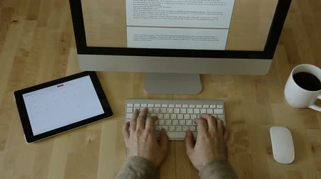 munka : All clear and in focus, of designer working at a wooden desk, with side view. text writing and journalistic work happening on a computer in the distance while designer Focuses on another monitor.
