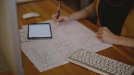 aletsiz : Young female architect working in office with blueprint signing details and making changes to the drawings. On the table lay a tablet, mouse and keyboard. on a video, we see a woman in modern clothes with a neutral polish, which holds a professional penci