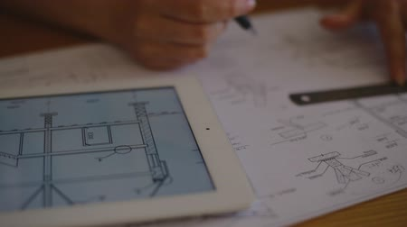 architektonický : female architect is checked against the electronic version of the drawing and making a change in the horizontal bemazhnuyu version with a ruler and pencil professional. Dostupné videozáznamy
