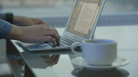 рабочих мест : Defocused transparent glass table with coffee. Close-up shot of female hands typing on notebook in public place.
