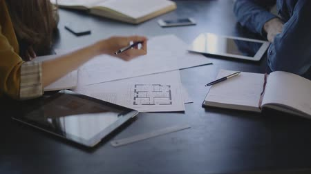 купить : Video artist and the customer order electrics are sitting across from each other and discuss the subject of the order, are actively working with papers, drawings. each has its own subject for the record, it is an electronic tablet, his paper notebook man
