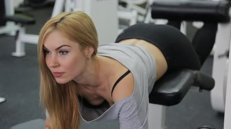 atletika : A strong athlete, blonde women with muscular body doing exercise on the buttocks and legs straining their muscles in the gym.