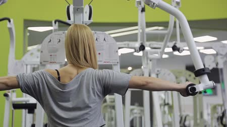 straining : A athlete, blonde women with muscular body doing exercise on the back and shoulders straining their muscles in the gym. Stock Footage