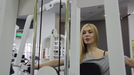 straining : A athlete, blonde women with muscular body doing exercise on the chest straining their muscles in the gym.