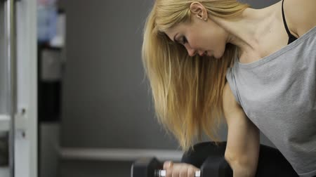 levantamento de pesos : A blond woman athlete doing exercise on the biceps in the arm straining their muscles, lifting dumbbell in the gym, with muscular body. Vídeos