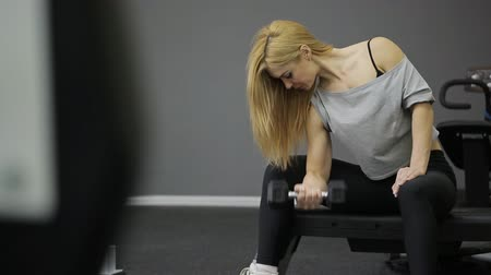 мышцы : A woman athlete doing exercise on the biceps in the arm straining their muscles, lifting dumbbell in the gym, with muscular body.