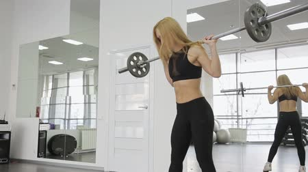 vzpírání : A muscular woman athlete using the barbell with weights, trains on the squats. buttocks, ass in the gym.