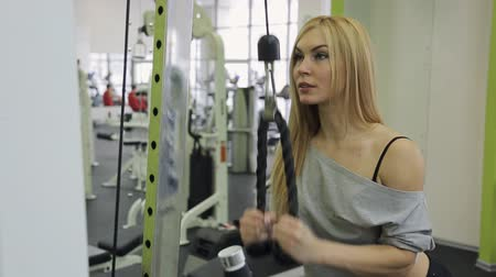 suor : A muscular woman athlete performs triceps strain on hand in the gym.