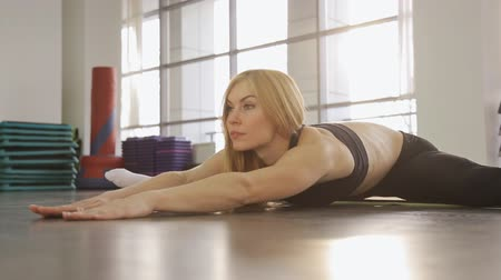 tornanti : Una donna bionda atleta facendo stretching in palestra. mentre nelle spaccature che si estende in avanti.