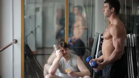tłuszcz : Sad tired fat man watches his athletic fellow training arm muscles with dumbbells