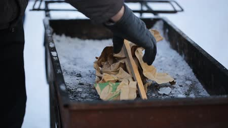briquettes : A man collects bonfire of paper of sticks in grill winter.