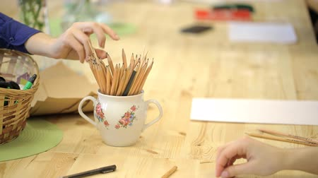 souprava : Cup with set of pencil on table, women take it, start to work. On table is empty sheet of paper