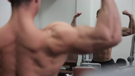 tükör : Bodybuilder in front of the mirror shows his huge muscles