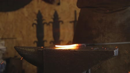 крупный план : Blacksmith puts on anvil billet a hot metal and begins to strike.