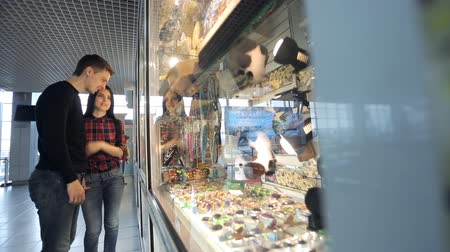 nákupy : Pretty couple of people regards souvenirs in shop in airport