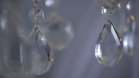 żyrandol : Shiny drops of sparkling crystals hang in air in white room