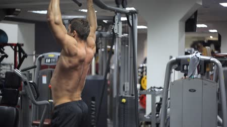 ayak parmakları : Male with an athletic build exercising on bar at gym.