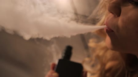 замена : Pretty blonde woman expires clubs of white fragrant smoke