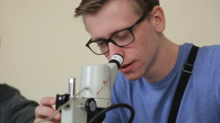 naukowiec : Young male student with glasses squinting looking into optical microscope.