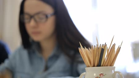proces : Young woman in glasses is drawing with a large number of ordinary pencils.