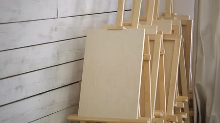 blank : Lots of wooden easels stand in corner of workshop