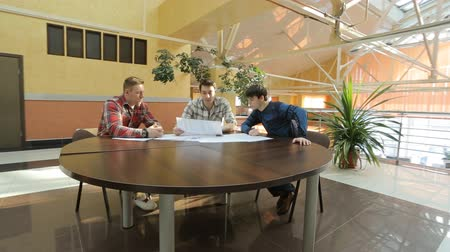 analyzovat : Three young architects sit at round wooden table and look at graphic