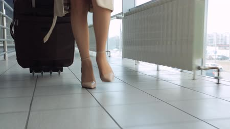 gates : Woman in heels goes at airport and roll suitcase on wheels.