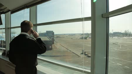 bezpieczeństwo : Airport Security Officer in uniform watching aerodrome traffic and talking on phone.