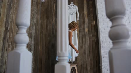 eleganckie : Beautiful blonde woman climbs on small stepladder to take her wedding dress.