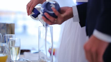 birlik : Newlyweds pour colorful sand in glass during wedding celebration.