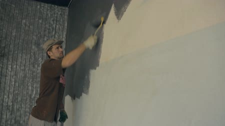 platen : Man is actively using a fur roller when painting walls gray paint. Stock Footage