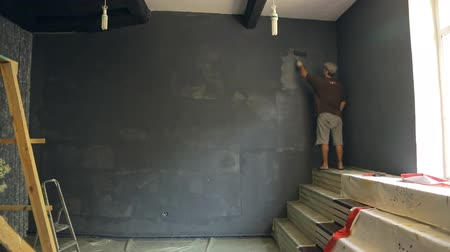 platen : Man paints wall for photo studio in a grey background with a roller, standing on stairs, near window. Stock Footage