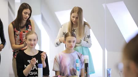 internar : Stylists create hairstyle for pretty girls in white studio