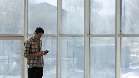 cellphone : A young man in a plaid shirt and a clock on hand, looking at smartphone screen, standing beside a panoramic window with a winter landscape.