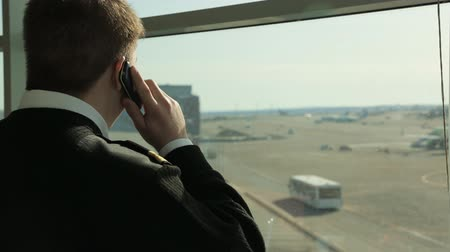 on the phone : Man in black sweater stands near window and talks on cell phone. Stock Footage