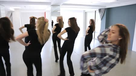 dança : Girls in black uniform actively dance in class on lesson of choreography