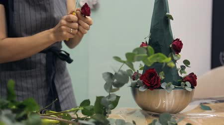 flower shops : Florist creates a fresh flower arrangement with roses and eucalyptus