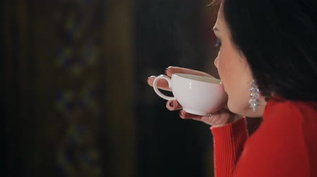 ital : Brunette in red sweater drinking hot tea inside restaurant