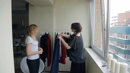 носить : Two women choose blue dress from rack with hangers in flat