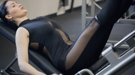 quads : Charming brunette exercise press legs on traineger in gym.