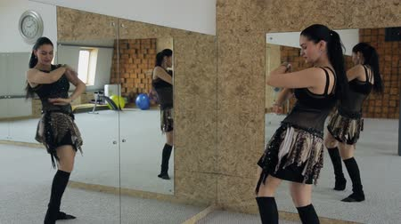 árabe : Beautiful woman dances belly dance in studio with many mirrors.